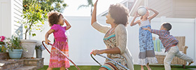 A woman and her children playing with hula hoops and a ball in their backyard.